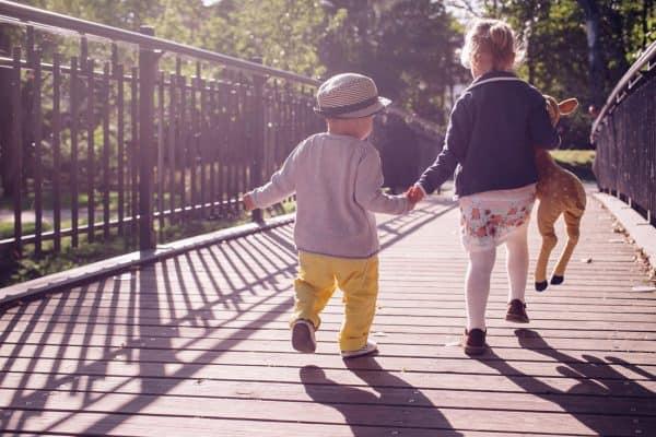 Kinder laufen Hand in Hand über ein Brücke
